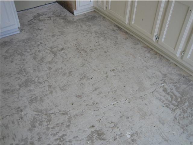 BEFORE- Cracked and pitted floor w/ tile glue